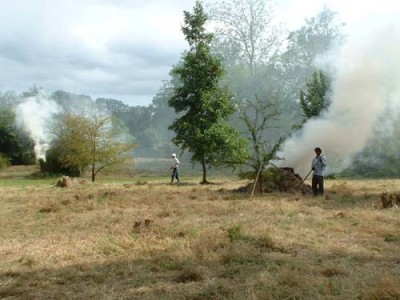 Volunteers mowing, raking and burning grass